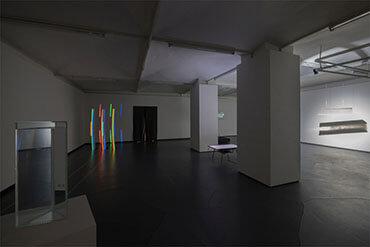 Blick vom Prisma auf die Wand, auf der man die zerlegten Farben sehen kann.